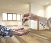 Realtor giving house key to buyer in empty room — Stock Photo