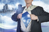 Businessman showing superhero suit underneath his shirt standing — Stock Photo