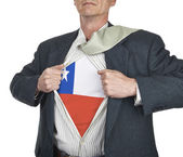 Businessman showing Chile flag superhero suit underneath his shi — Stock Photo