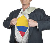 Businessman showing Colombia flag superhero suit underneath his  — Stock Photo