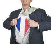 Businessman showing French flag superhero suit underneath his sh — Stock Photo