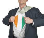 Businessman showing Ivory Coast flag superhero suit underneath h — Stock Photo