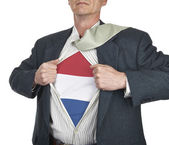 Businessman showing Netherlands flag superhero suit underneath h — Stock Photo
