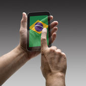 Holding Brazil flag screen smart phone — Stock Photo