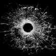 Bullet hole in glass isolated on black — Stock Photo
