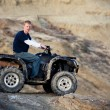 Teen on quad ATV in the hills - Stock Photo