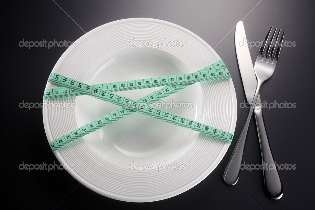 Plate tied with green tape measure with fork and knife — Stock Photo #12708289