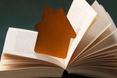 Golden house and book — Stock Photo