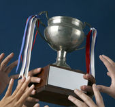 Human hands holding a silver trophy. — Stock Photo