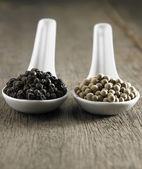 Black and white peppercorns — Stock Photo