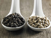 Black and white peppercorns — Stock Photo