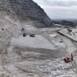Italy, Maddaloni (Naples), stone pit with industrial vehicles at work - Стоковая фотография