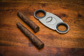 Italy, italian cigars (toscani) and a cigars cutter on a wooden table — Stock Photo