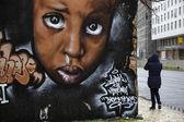 Mujer de portugal, lisboa, caminando por una pintura mural en una pared al centro — Foto de Stock