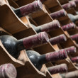 Old red wine bottles aging in a wine cellar — Stock Photo