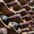 Stock Photo: Old red wine bottles aging in wine cellar