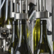 Italy, Sicily, wine bottles filled with wine by an industrial machine in a wine factory - 图库照片