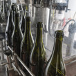 Italy, Sicily, wine bottles being washed and filled with wine by an industrial machine in a wine factory - Stockfoto