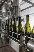 Italy, Sicily, wine bottles being washed and filled with wine by an industrial machine in a wine factory — Stock Photo