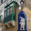 Victoria city, typical maltese window and a religious statue - Stock Photo
