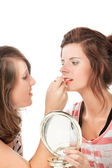 Two teenage girl putting on make-up — Stock Photo