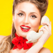 Stock Photo: Pin-up girl talking on retro telephone