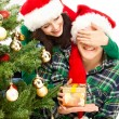 Young happy couple near a Christmas tree. — Стоковая фотография