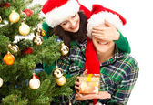 Young happy couple near a Christmas tree. — Stock Photo