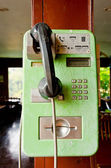 Green phone on old wood — Stock fotografie