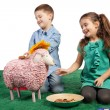 Laughing children playing with a toy sheep - Stock Photo
