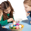 Three children painting Easter eggs - Stock Photo
