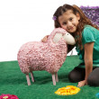 Little girl cudddling a toy sheep - Stock Photo