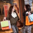 Happy woman shoppers in a mall - Stock Photo