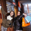 Playful shoppers with lots of purchases - Stock Photo
