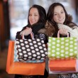 Two happy women holding shopping bags - Stock Photo