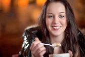 Smiling woman eating froth off her cappuccino — Stock Photo
