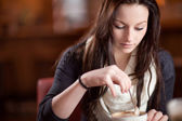 женщина, перемешивание чашку капучино — Стоковое фото