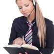 Woman wearing a headset taking notes - Stock Photo