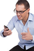 Angry young man looking at his mobile phone — Stock Photo