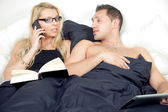 Woman taking a call in bed — Stock Photo