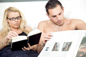 Attractive couple reading in bed together — Stock Photo