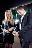 Stylish couple opening a bottle of champagne — Stock Photo