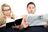 Amicable couple reading in bed together — Stok fotoğraf