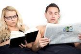Vänskaplig par läsning i sängen tillsammans — Stockfoto