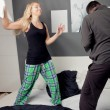Young couple having a pillow fight — Stockfoto