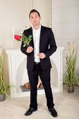 Romantic suitor carrying a red rose — Stock Photo