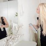 Woman applying hairspray to her hair — Stock Photo