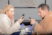 Couple checking their mobile phones at breakfast — Stock Photo