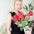 Man presenting a woman with red roses — Stock Photo