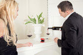 Man pouring red wine with a open ring box — Stock Photo